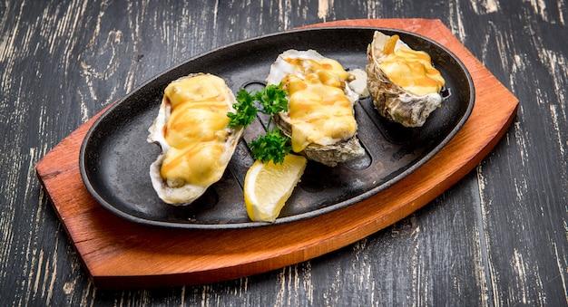 Ostriche in padella con salsa cremosa e formaggio Foto Premium