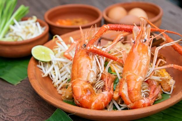 Pad thai o thai style noodle saltati in padella con gamberetti interi Foto Premium