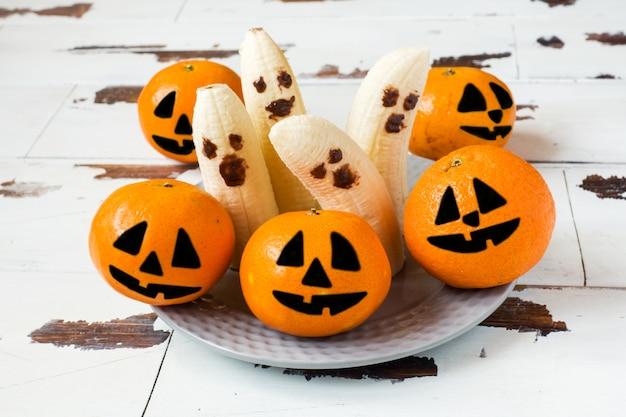 Volti divertenti dipinti su mandarini e banane per halloween Foto Premium