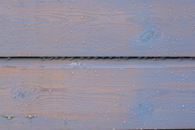 Sfondo di recinzione in legno verniciato con goccioline di acqua piovana, bagnato, un sacco di struttura in legno a contrasto, orizzontale Foto Premium