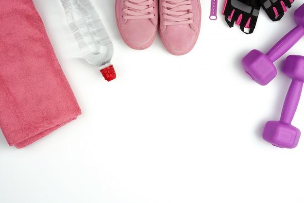 Paio di sneaker in pelle rosa, manubri in plastica e guanti per lo sport Foto Premium