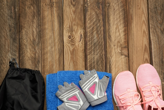 Paio di scarpe da ginnastica rosa, asciugamano blu e guanti per lo sport Foto Premium