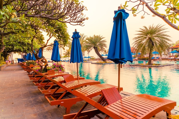 Palma con sdraio ombrellone in resort hotel di lusso a volte alba Foto Premium