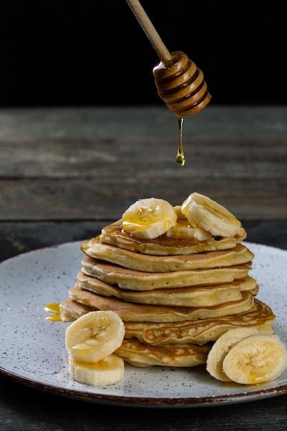 Frittelle sul piatto in ceramica servito con banane e miele su legno Foto Premium