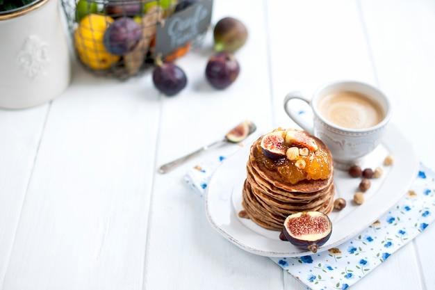 Frittelle con marmellata e fichi su un piatto bianco e una tazza di caffè su uno sfondo bianco Foto Premium
