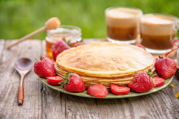 Frittelle con fragole e caffè per colazione. Foto Premium