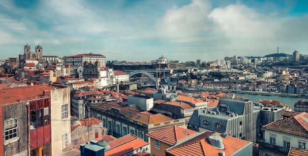 Panorama del centro storico con tetti di tegole rosse e il ponte don luis a porto portogallo una soleggiata giornata di primavera Foto Premium