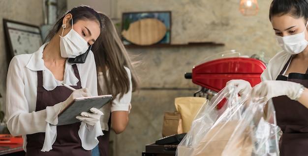La cameriera asiatica panoramica prende l'ordine dal telefono cellulare per ordini di ritiro da asporto o dal marciapiede. Foto Premium