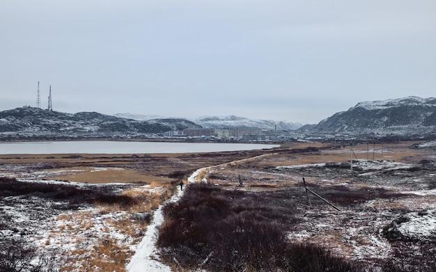 Vista panoramica uno stretto sentiero che porta in lontananza al villaggio artico situato tra le colline polari Foto Premium