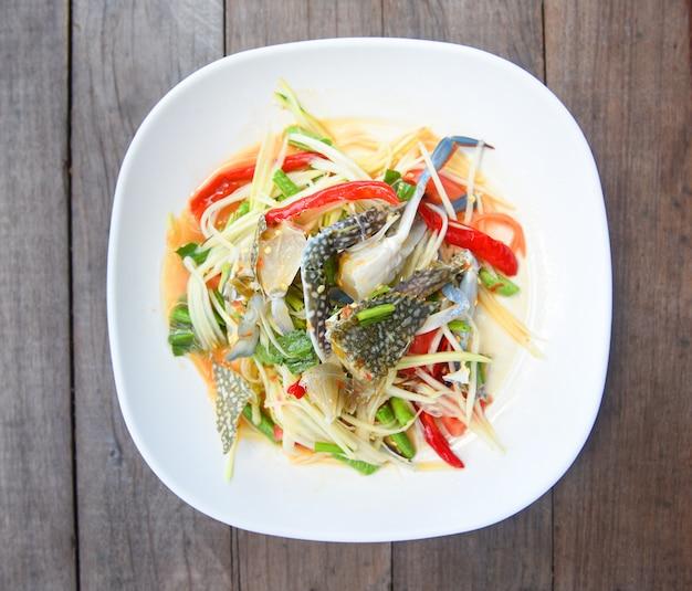 Insalata della papaia con il granchio blu / frutti di mare e la verdura piccanti dell'insalata del granchio crudo tailandese dell'alimento sulla tavola di legno Foto Premium