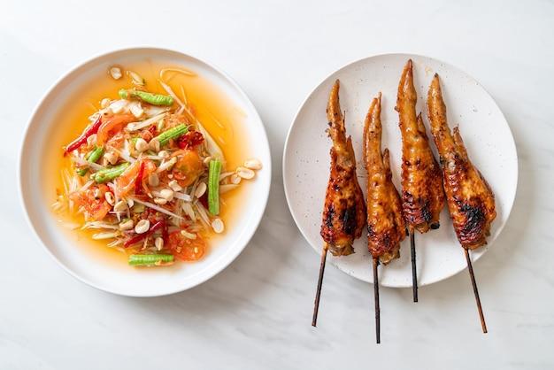 Insalata piccante di papaya con pollo alla griglia - stile di cibo di strada tradizionale tailandese Foto Premium
