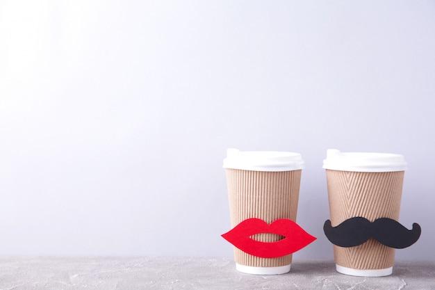 Tazza di caffè di carta con la decorazione delle labbra e dei baffi su gray. san valentino e concetto di matrimonio. Foto Premium