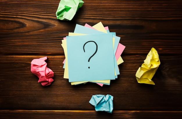 Adesivi di carta con un punto interrogativo su un fondo di legno Foto Premium