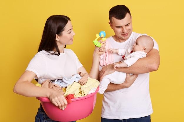 I genitori che si prendono cura del neonato mentre fanno le faccende domestiche e il bucato, la madre con i capelli scuri che mostra il sacco di fagioli al loro bambino, più grasso tiene il bambino in mano, isolato su sfondo giallo. Foto Premium
