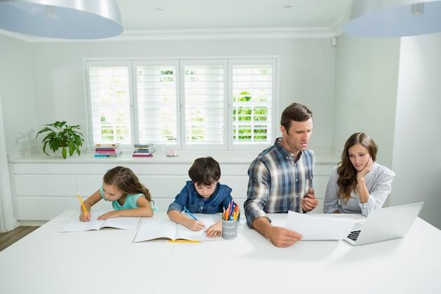 Genitori che lavorano con il computer portatile e bambini che studiano nel salone Foto Premium