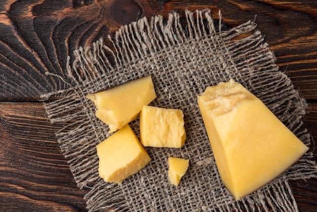 Parmigiano su fondo di legno scuro. Foto Premium