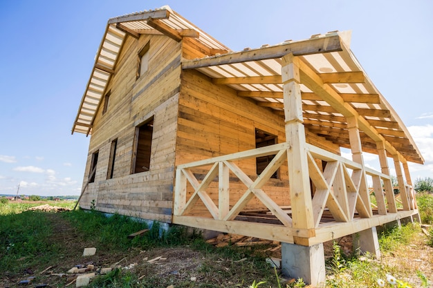 Parte del cottage ecologico tradizionale in legno grezzo di materiali in legno naturale con struttura del tetto ripido e terrazza attaccata con ringhiera decorativa in costruzione nel quartiere verde. Foto Premium
