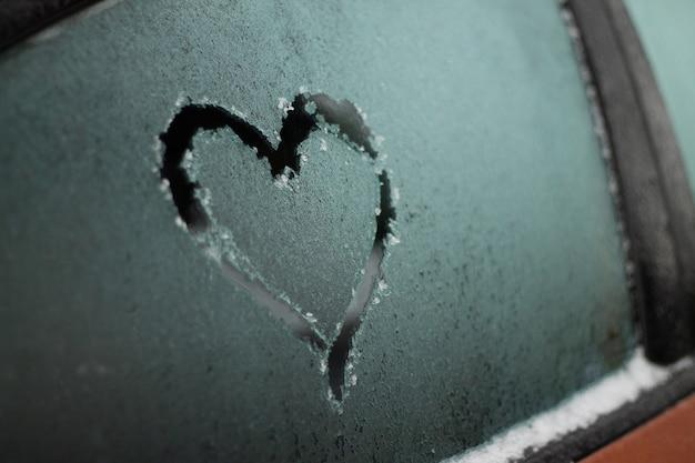 Cuore parzialmente sfocato disegnato con un dito sul finestrino congelato di un'auto arancione in inverno, fuoco selettivo, copia dello spazio Foto Premium