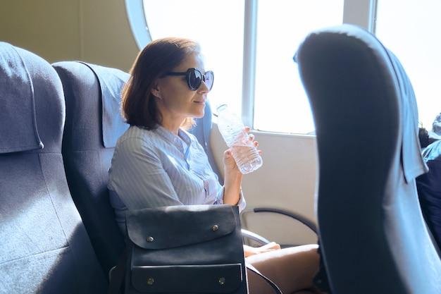 Trasporto di passeggeri, donna seduta all'interno di un comodo traghetto marittimo Foto Premium