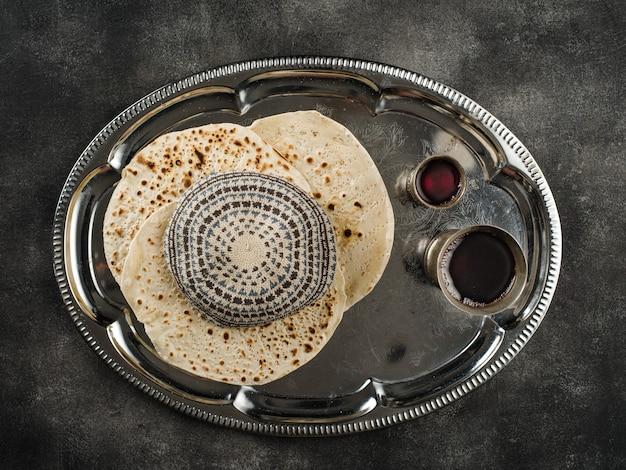 Pasqua ebraica pane azzimo pane festivo ebraico, due bicchieri di vino kosher e kippa sul tavolo di pietra. Foto Premium