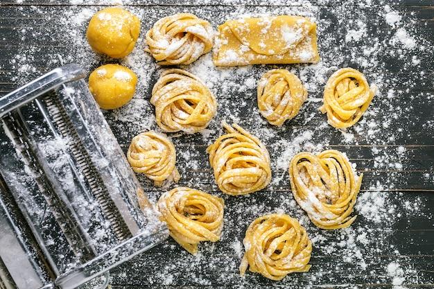 Pasta con ingredienti di pasta sulla vista superiore del tavolo in legno scuro Foto Premium