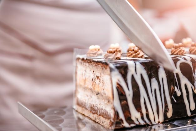 Pasticcere prendendo fetta di torta Foto Premium