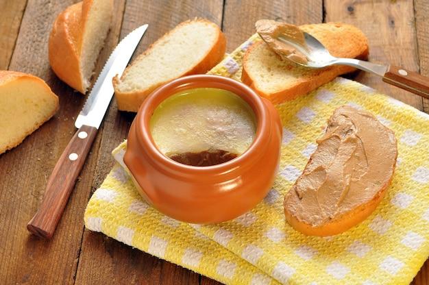 Pate in una pentola di ceramica e tostate la pagnotta su un tovagliolo. cucchiaio e coltello su fondo di legno Foto Premium