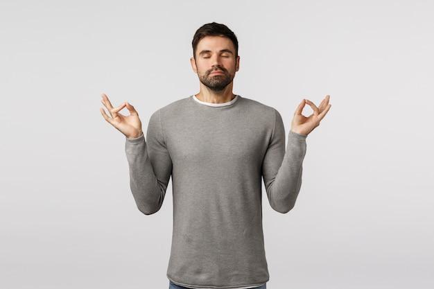 Concetto di pazienza, relax e meditazione. il giovane ragazzo barbuto bello pacifico allarga la mente e il corpo, si sente zen, solleva il gesto di mudra delle mani, pratica lo yoga di respirazione con gli occhi chiusi Foto Premium