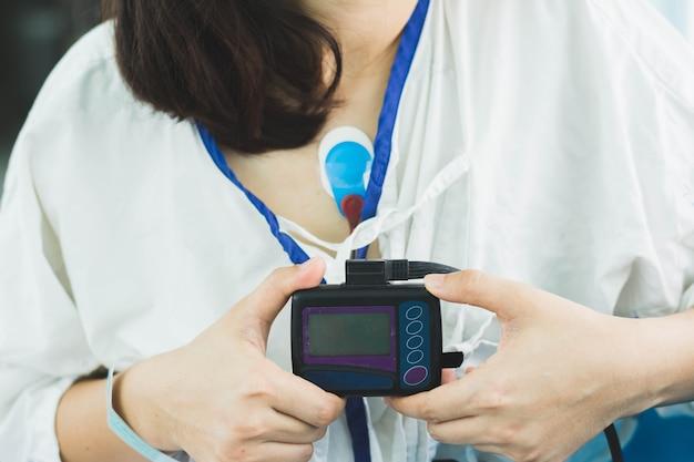 Paziente che indossa un dispositivo di monitoraggio holter per il monitoraggio di un elettrocardiogramma su 24 ore di indagine cardiaca Foto Premium