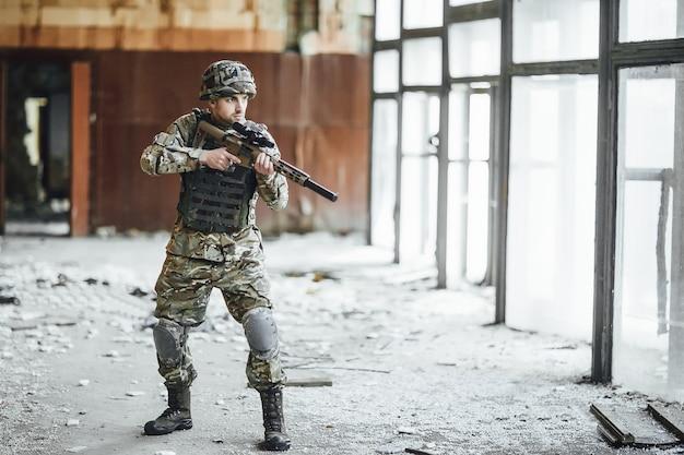 Pattuglia il territorio. il giovane soldato militare si trova alla finestra dell'edificio crollato. sulla testa c'è un elmetto protettivo. c'è una grande pistola nelle sue mani! Foto Premium