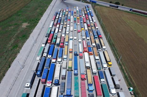 Un modello di molti camion smontati da un'altezza. camion in fila per scaricare il grano al porto. Foto Premium