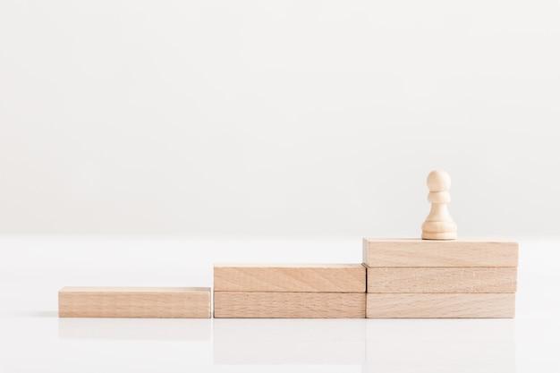 Pezzo degli scacchi pedina su una scala di mattoni di legno, concettuale della visione aziendale. Foto Premium