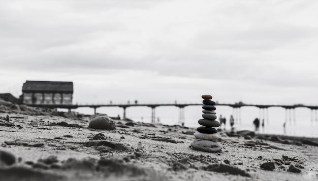 Torre di ciottoli in riva al mare con molo sfocato fino al mare Foto Premium