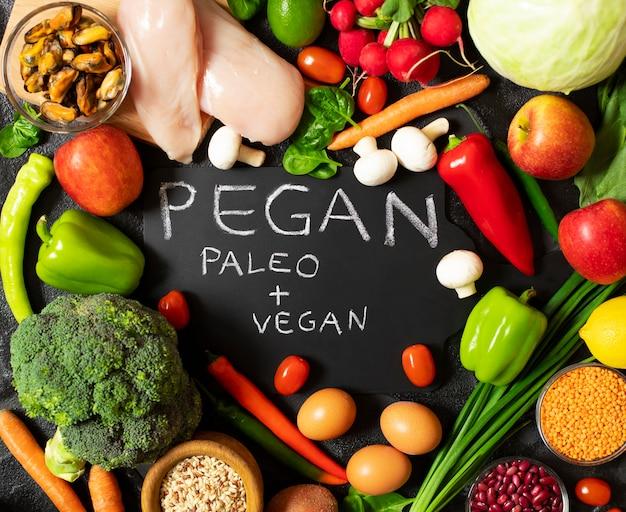Dieta pegan. combinazione di diete vegane e paleo. cibo sano - assortimento di frutta e verdura fresca, pollo, uova, cozze, legumi, funghi. Foto Premium