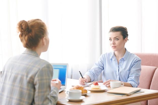 Pensierose donne d'affari moderne sedute a tavola con tazze di caffè e dessert e discutendo l'attuazione del progetto durante il pranzo Foto Premium
