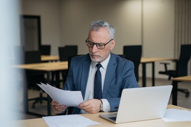 Contratto di lettura senior pensieroso dell'uomo d'affari. ritratto del maschio bello che lavora con i documenti in ufficio Foto Premium