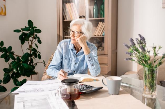 Donna senior pensierosa che conta le tasse Foto Premium
