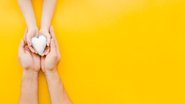 Persone in possesso di un cuore bianco nelle mani con spazio di copia Foto Premium