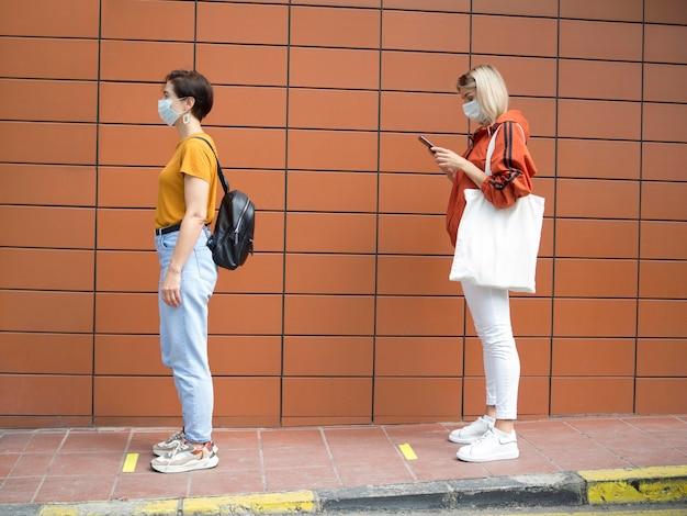 Persone che mantengono il concetto di distanza sociale Foto Premium