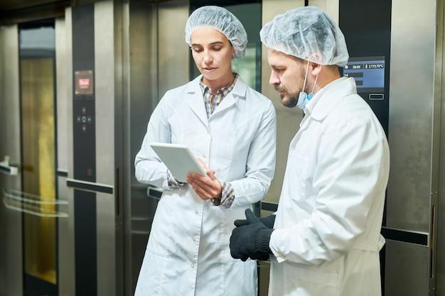 Persone in camici da laboratorio in piedi e utilizzando la tavoletta Foto Premium