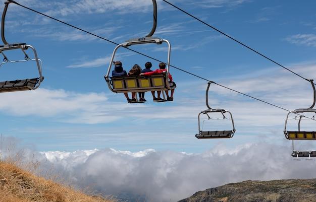 Persone in sella alle seggiovie delle stazioni sciistiche, guardando le montagne e l'orizzonte, indietro Foto Premium