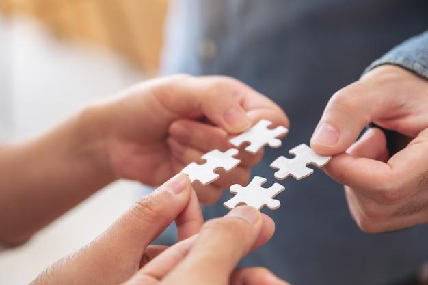 Le mani della gente che tengono e mettono insieme un pezzo di puzzle bianco Foto Premium
