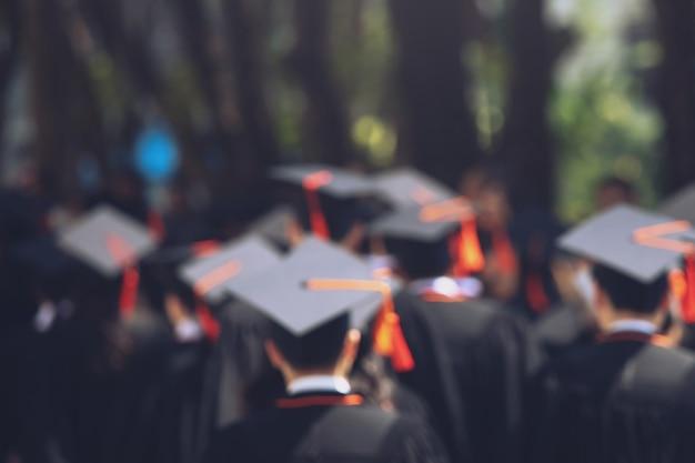 La gente mostra il cappello di spettacolo della stretta della mano nappe blu nella priorità bassa edificio scolastico. colpo del tappo di laurea durante il concetto di laurea universitaria di inizio, concetto di apprendimento di successo dello studente di educazione di celebrazione Foto Premium