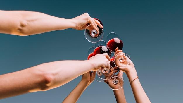 Persone che tostano il primo piano del vino dal basso Foto Premium