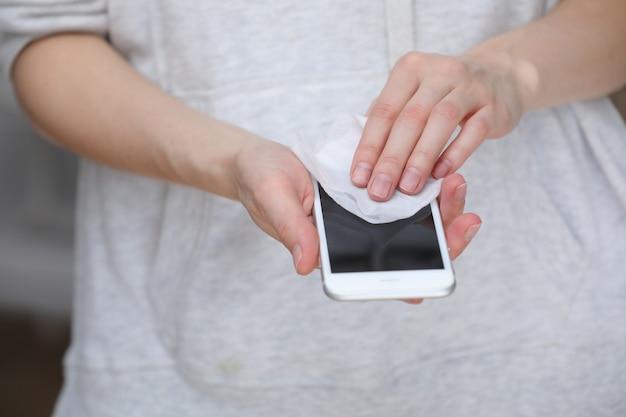 Schermo del telefono cellulare person cleaning con salviettine disinfettanti per smartphone pulito. Foto Premium