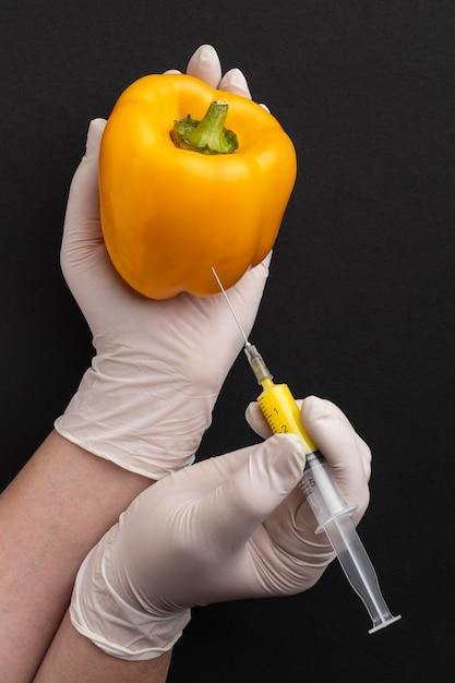 Persona in possesso di peperone dolce e siringa Foto Premium