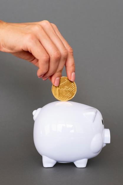 Persona che mette in monete bianche del porcellino salvadanaio Foto Premium