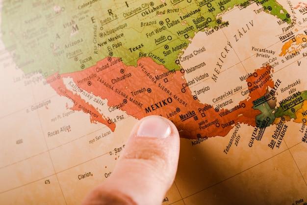 Il dito di una persona che mostra città del messico sulla mappa Foto Premium
