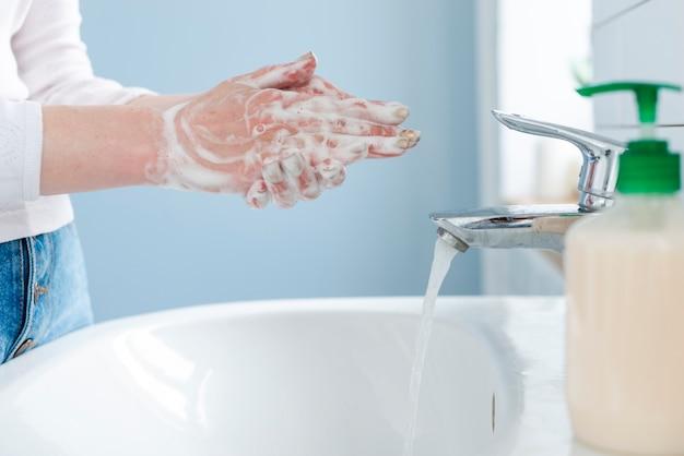Persona che si lava le mani con acqua e sapone Foto Premium
