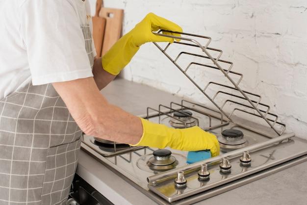 Persona che lava la stufa con i guanti Foto Premium